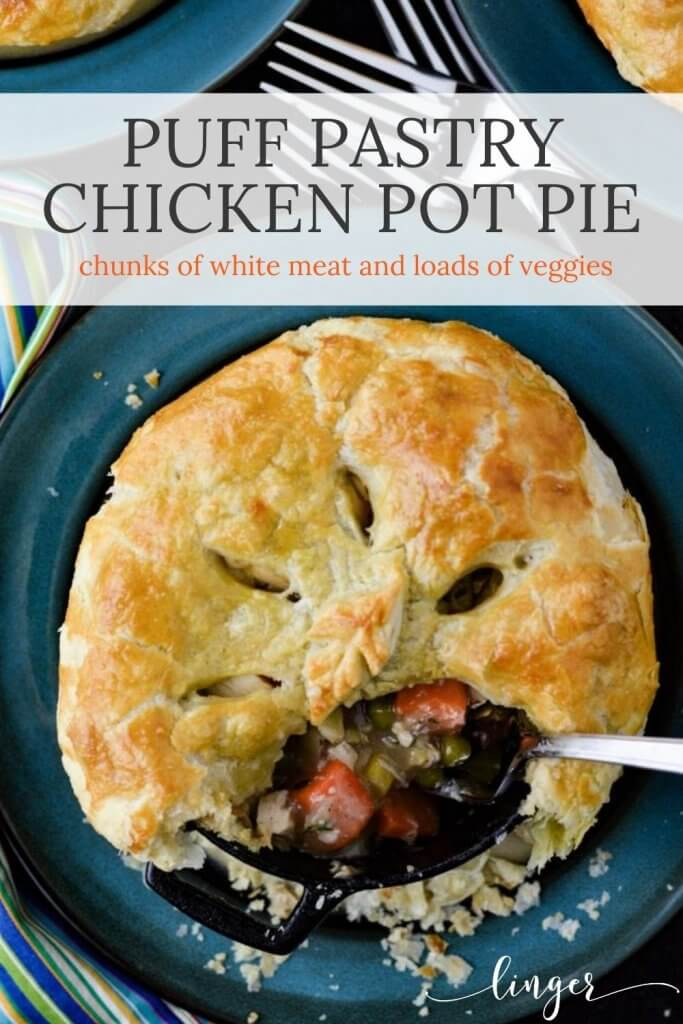 A chicken pot pie with a puff pastry that has slits in the top. A scoop has been taken out and has a fork in it. The pot pie sits on a blue saucer. Forks are in the middle of the photo with a blue striped napkin next to the plate.