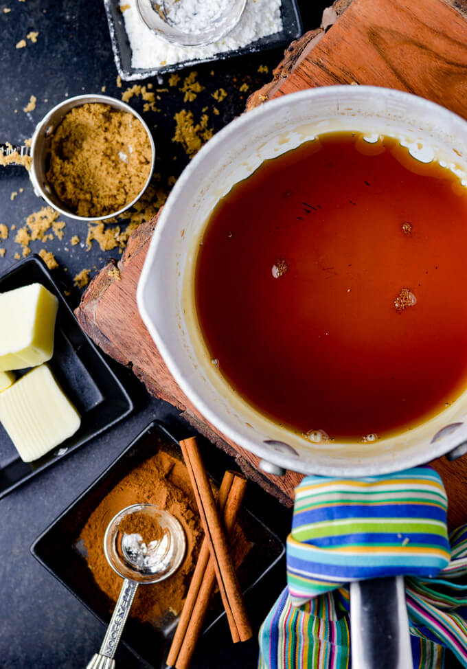 A pan of amaretto syrup sitting on large board pot holder. A measuring cup of brown sugar, and 3 small black saucers with cubes of butter, cornstarch and cinnamon are next to the pan. A blue striped napkin is wrapped around the handle of the pan.