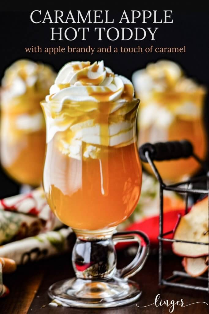 Three caramel apple hot toddy with whipped cream and caramel sauce dripping down the side. A small basket of dried sliced apples sit next to it. A colorful napkin sits next to the glasses.