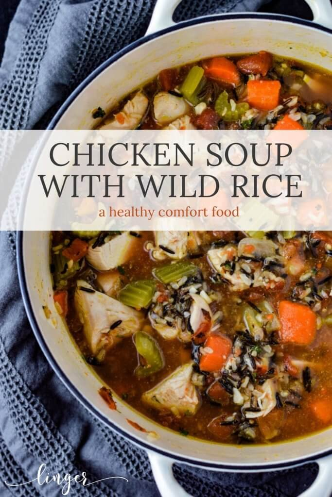 A Dutch oven of wild rice chicken soup with carrots, onions and celery. A Gray napkin sits next to the pot.
