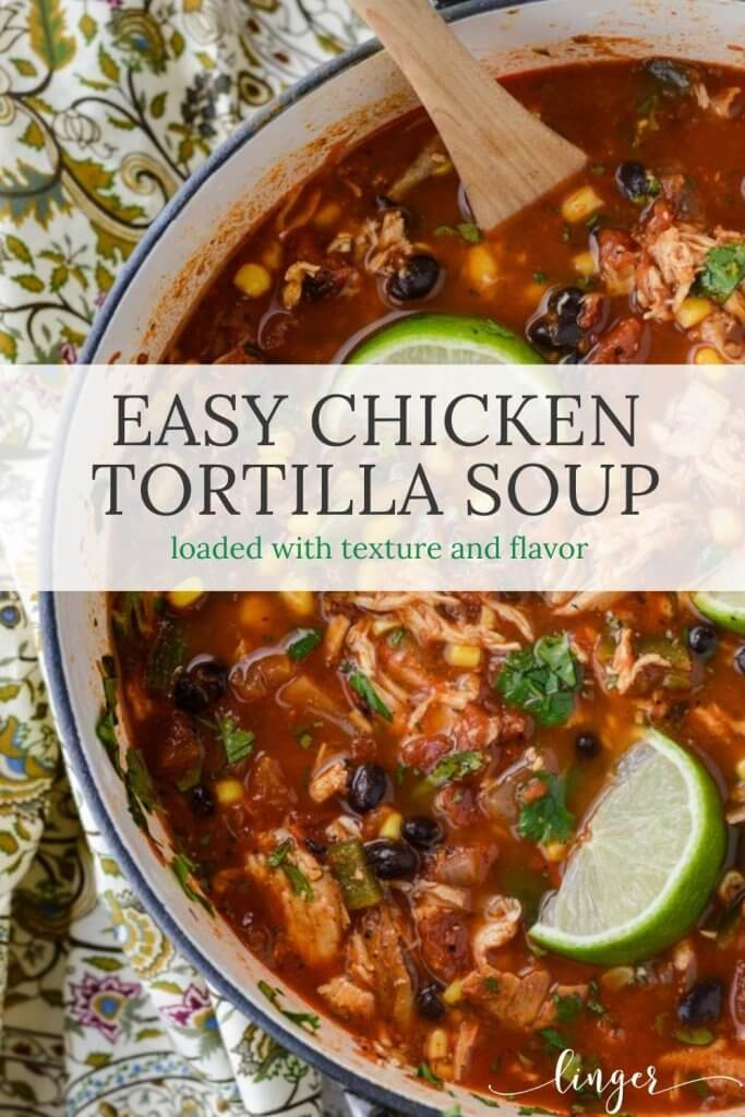 A Dutch Oven of homemade Chicken Tortilla Soup. Three lime wedges sit on top of the soup with a few cilantro leaves scatter on top.