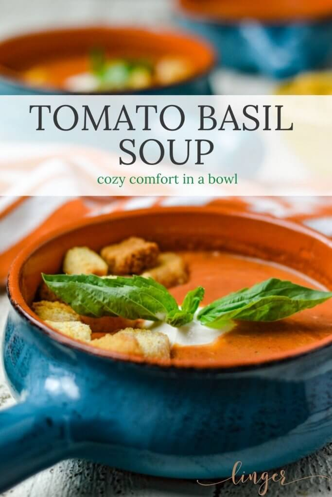 Tomato Basil Soup sits in a blue bowl with a dollop of sour cream, a sprig of fresh basil and croutons. A white and orange striped napkin, two more bowls of soup and a yellow bowl of croutons are blurred in the background.