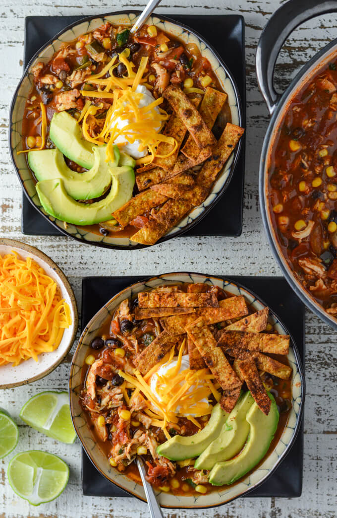 Two black bowls of homemade chicken tortilla soup sit on black plates. Each soup has sliced avocados, tortilla strips, a dollop of sour cream and shredded cheese on top of it. A Dutch Oven with the soup sits off to the side. Wedges of limes and a small bowl of shredded cheese sit on the other side.