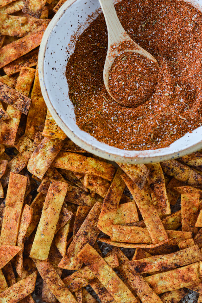 A pile of homemade baked tortilla strips with spices on them and a bowl of the spices sit in the corner of the photo.