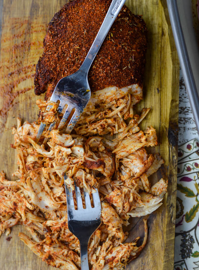 A partly shredded piece of spicy chicken sits on a wooden cutting board with two forks shredding the chicken.