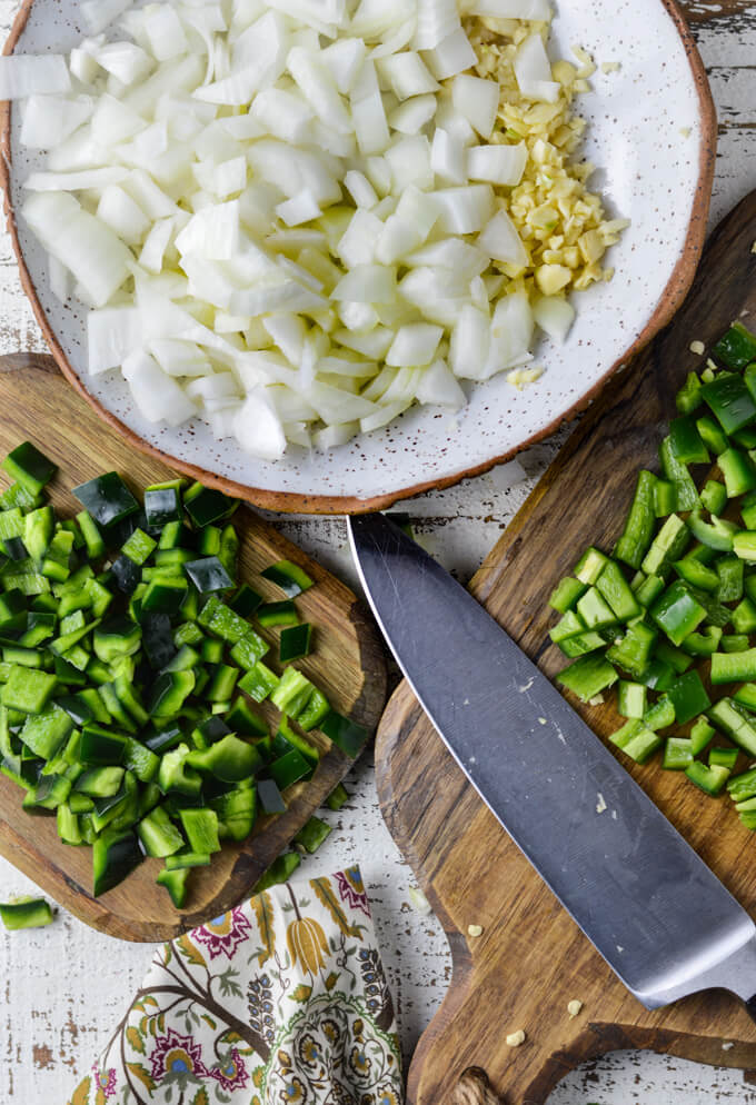 A bowl of chopped onions and garlic with two wooden cutting boards having chopped poblano and jalapeno peppers on them. A chopping knife sits on one of the cutting boards.