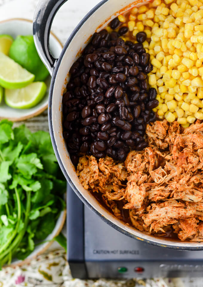 A Dutch Oven has the makings of a Chicken Tortilla Soup. Black beans, frozen corn and spicy shredded chicken sit divided in the pan. Cilantro and cut up limes sit next to the pan.