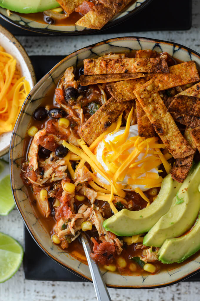 A close-up photo of a bowl of homemade chicken tortilla soup with tortilla strips, slices of avocado, a dollop of sour cream and shredded cheese. A small bowl of shredded cheese and some cut up limes sit next to the bowl of soup.