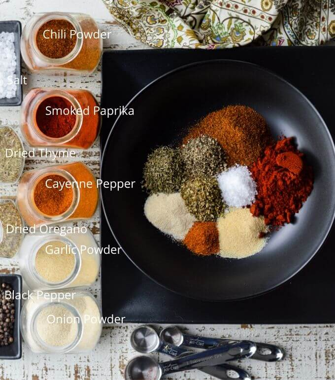 A black bowl with spoonfuls of spices. A napkin sits at the top of the photo and measuring spoons at the bottom. Jars of spices and salt and pepper sit next to the bowl.