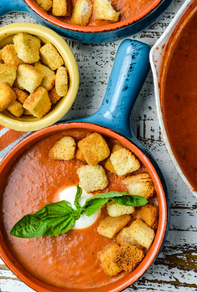 Homemade tomato soup in two blue bowls with a dollop of sour cream, fresh basil sprigs and croutons. A small bowl of croutons and a pot of tomato soup sit next to the bowls along with an orange and white striped napkin.