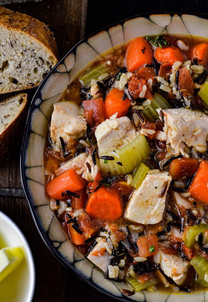 A bowl of wild rice chicken soup with carrots, onions and celery.