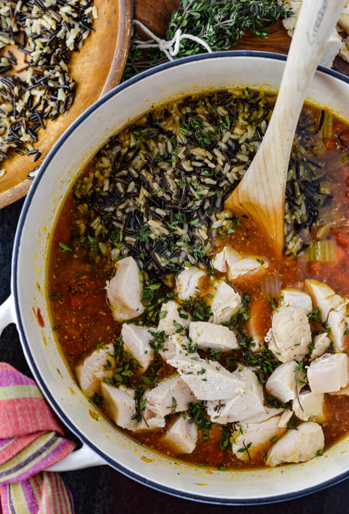 A Dutch oven with broth, veggies, wild rice and chunks of chicken.