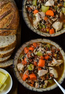 Two bowls of wild rice chicken soup loaded with carrots, onions and celery. A sliced load of bread with a small white bowl of butter cubes sit next tot he soup.