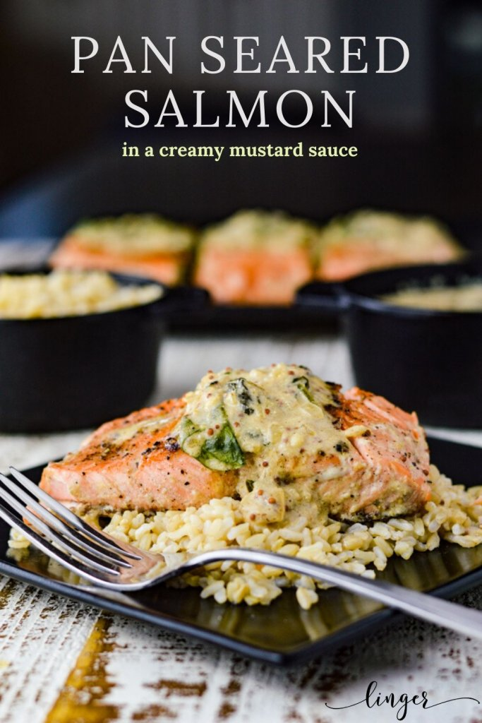 A side photo of pan-seared salmon fillet with creamy mustard sauce on a bed of brown rice. Bowls of brown rice and cream sauce sit in the background. Three other salmon fillets are blurred in the background.
