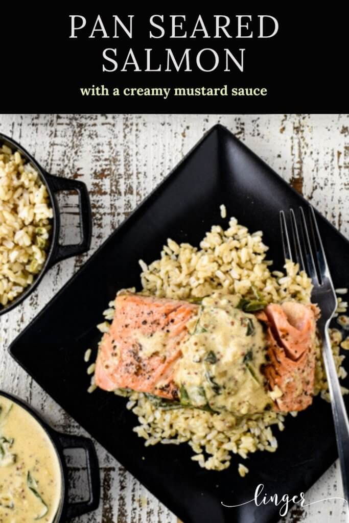 A black plate with a pan-seared salmon fillet on a bed of rice with a creamy mustard and spinach sauce. A bowl of brown rice and a bowl of creamy mustard sauce sits next to the salmon.