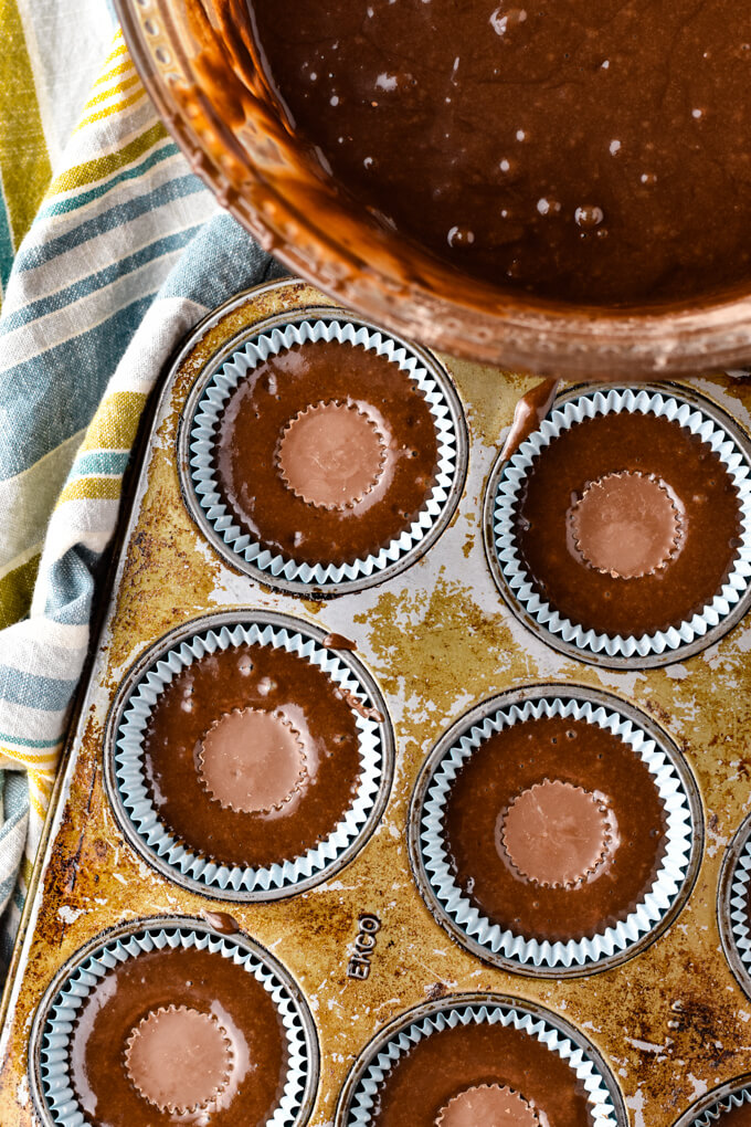 A muffin tin with blue cupcake liners are filled with chocolate cake and a mini reeses cup sits in the middle of the cake batter. A bowl of cake batter sits in the corner of the photo and a blue and yellow striped napkin sits next to the pan.