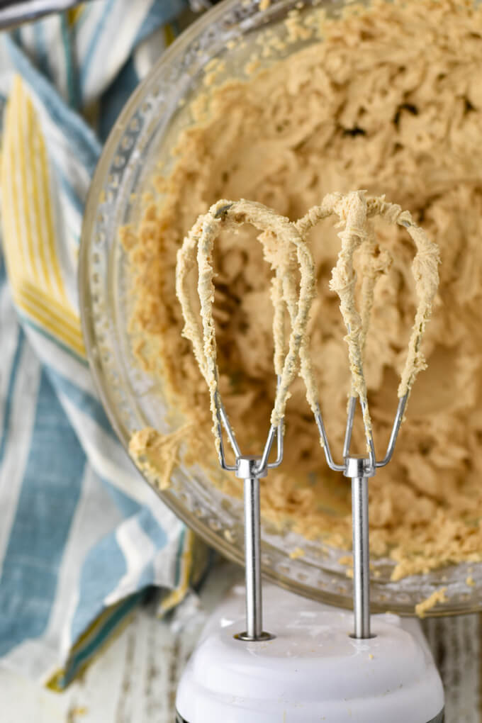 A clear glass mixing bowl holds creamed peanut butter frosting with 2 egg beaters sitting over the top. A blue and yellow striped napkin sits next to it.