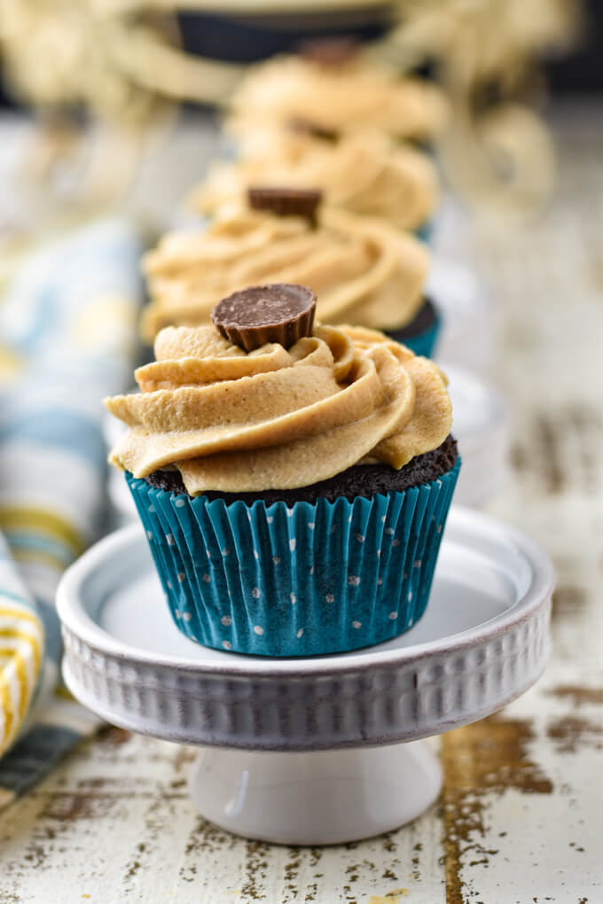 A chocolate peanut butter cupcake in a blue liner sits on a mini cake stand with 3 other cupcakes blurred in the background.