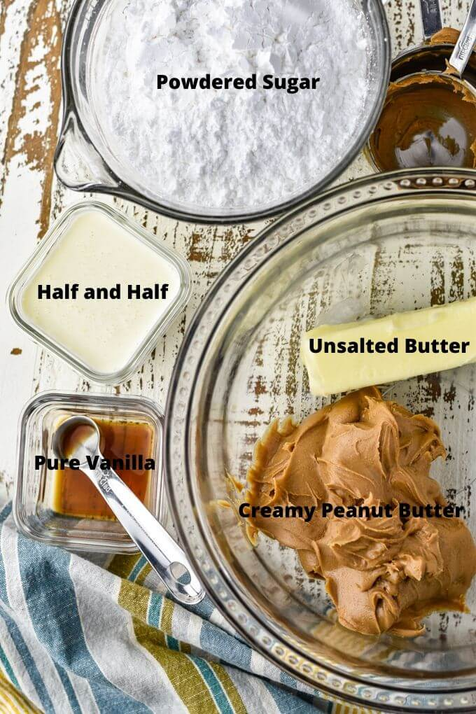 A clear glass mixing bowl holds peanut butter and a stick of butter. Preps bowls with half and half and pure vanilla sit next to it. Also a bowl of powdered sugar and empty measuring cups sit next to the bowl.