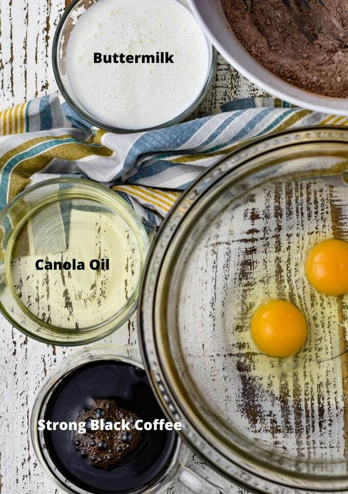 A clear glass mixing bowl holds 2 cracked eggs. A dry mixture sits in the corner of the photo. Two clear small bowls of buttermilk and oil along with a clear cup of black coffee sit next to the mixing bowl.