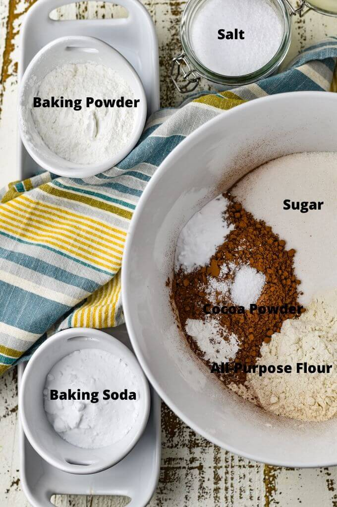 A white mixing bowl holds sugar, flour, cocoa, salt, baking powder and baking soda. A blue and yellow striped napkin sits next to the bowl with prepping bowls of baking soda, baking powder and salt next to it.