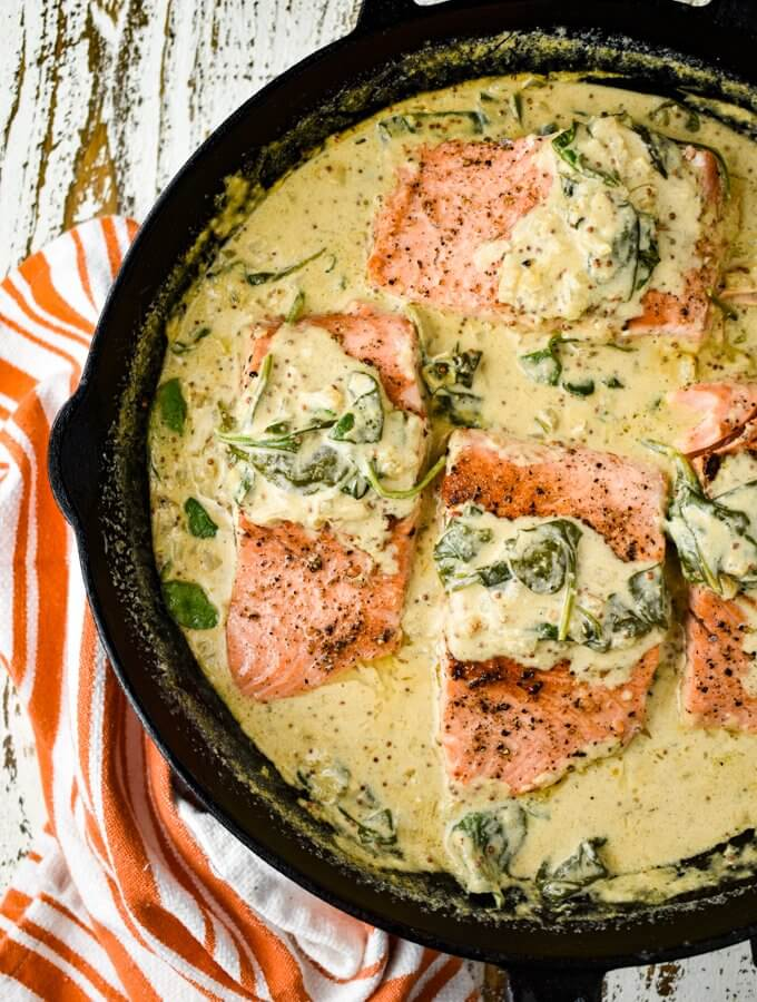 Four pan-seared salmon fillets sit in a creamy mustard and spinach sauce in a cast-iron skillet. A orange and white striped towel sits beside the pan.