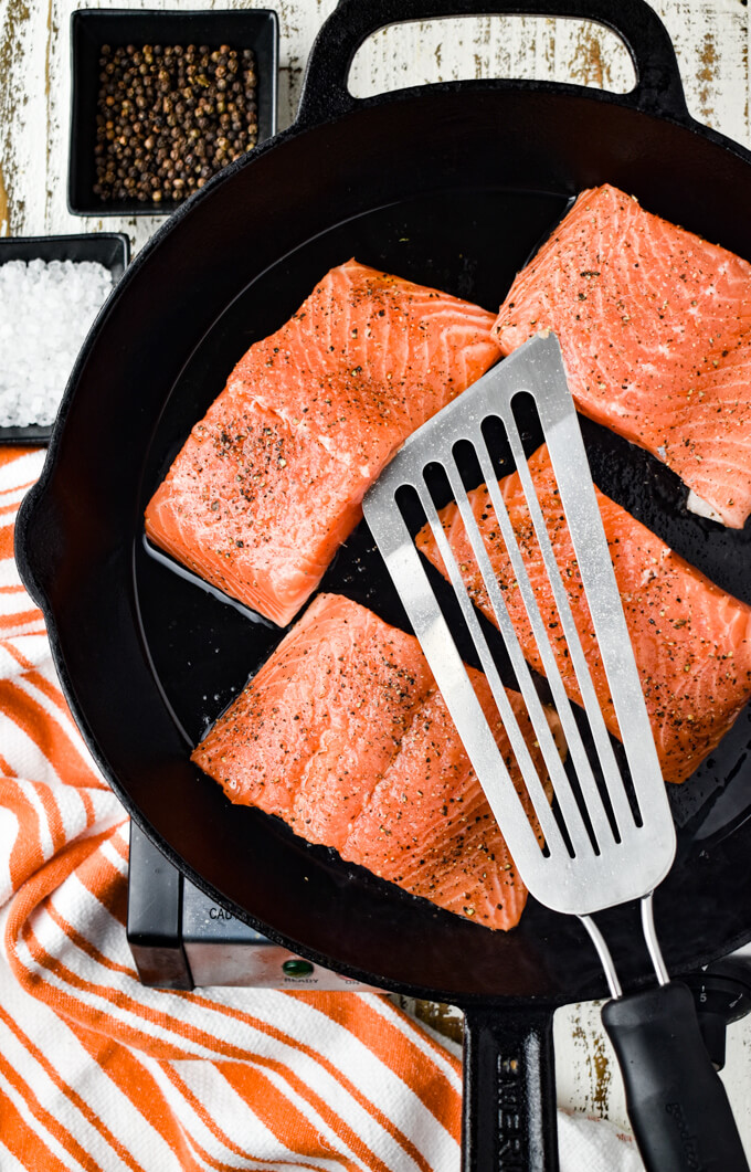 Four salmon fillets cooking in a cast iron skillet. A fish spatula sits on top and orange and white towel sits next to the pan.