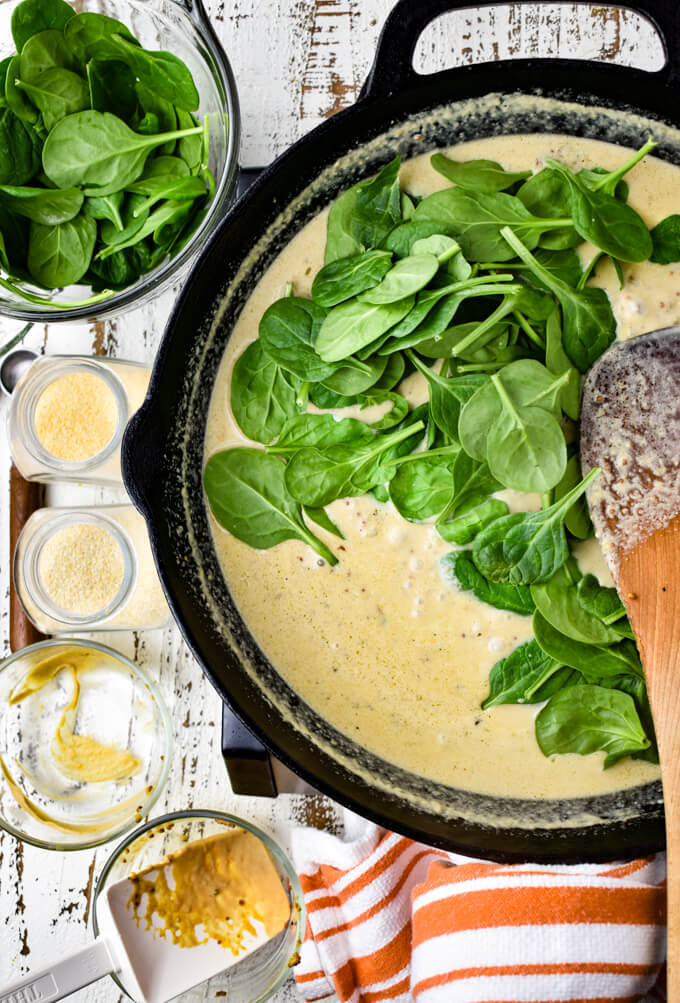 A cast iron skill with creamy mustard sauce and fresh spinach on top,. Empty prep bowls sit next to the skillet.