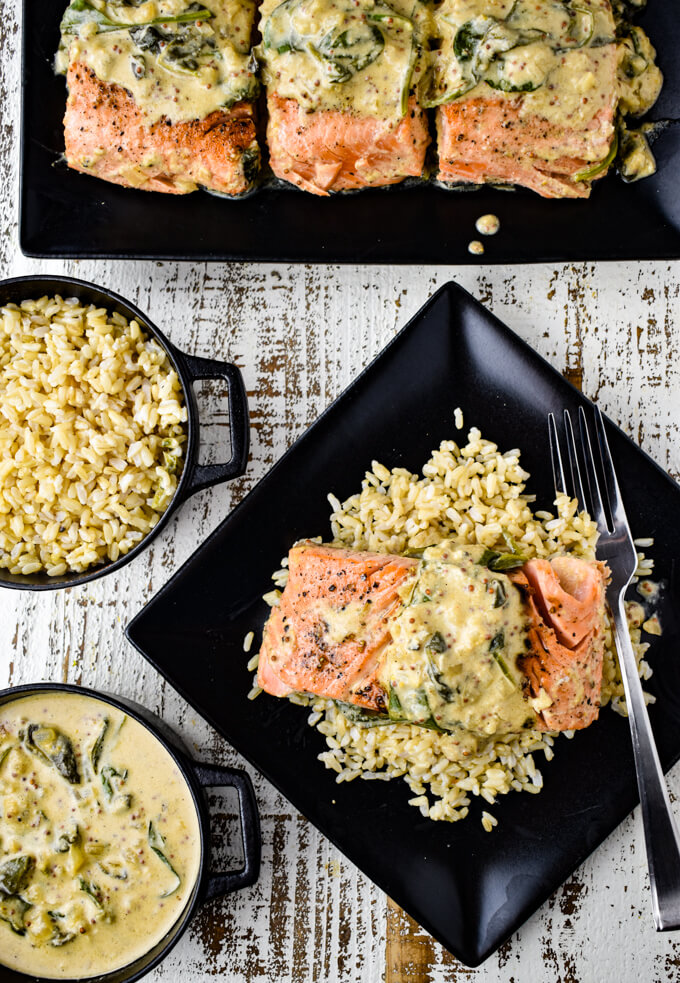A black plate with a pan-seared salmon fillet on a bed of rice with a creamy mustard and spinach sauce. Three fillets sit on a black plate in the top of the photo. A bowl of brown rice and a bowl of creamy mustard sauce sits next to the salmon.