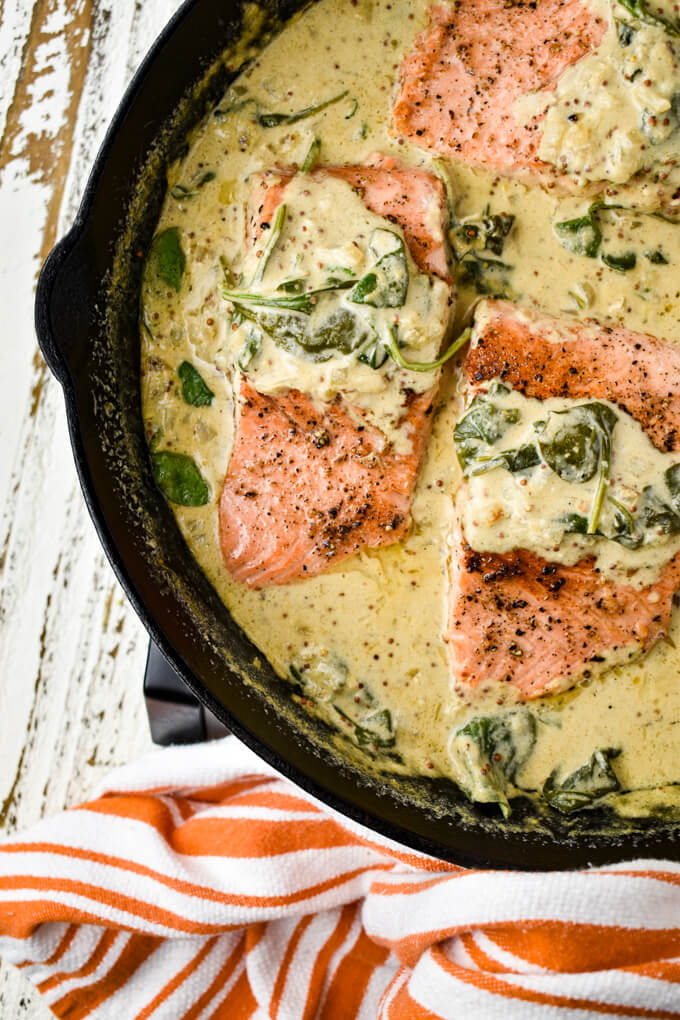 Three pan-seared salmon fillets sit in a creamy mustard and spinach sauce in a cast-iron skillet. A orange and white striped towel is around the handle.