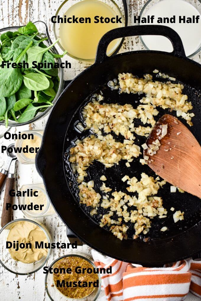 A cast iron skillet with sauteed onions and garlic in it for a pan-seared salmon recipe. Prep bowls hold half and half, chicken stock, fresh spinach, onion powder, garlic powder, dijon mustard and stone ground mustard.