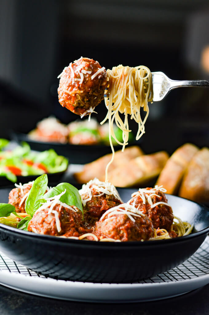 A bowl of spaghetti and meatballs. A fork holding swirled spaghetti noodles and a meatball hangs over the plate. A green salad, bread and another bowl of spaghetti sit blurred in the background.