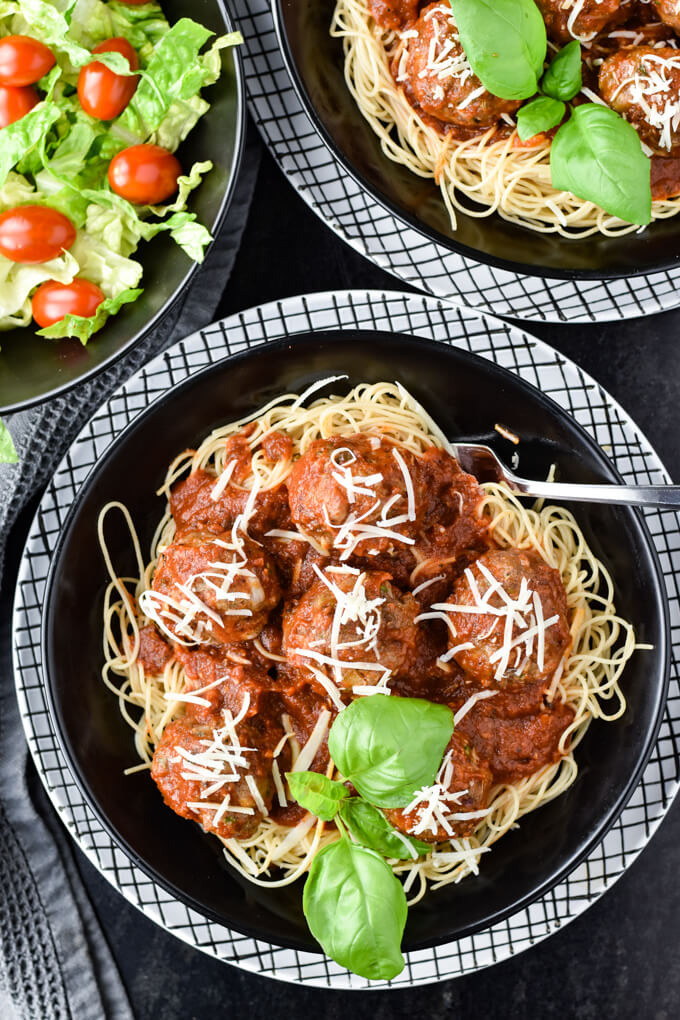 A black bowl of homemade spaghetti and meatballs on a white checkered plate. A salad and another bowl of spaghetti and meatballs sit in the corner of the photo.