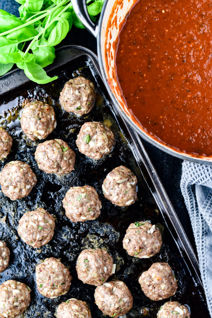 Cooked meatballs on a baking sheet with a pan of spaghetti sauce and fresh basil leaves next to it.