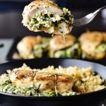 A fork holds a bite of spinach stuffed chicken breast over a black bowl of rice and stuffed chicken. Three stuffed chicken breasts are blurred in the background.