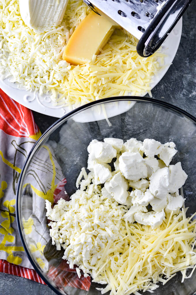 A clear glass mixing bowl holds fresh mozzarella, grated parmesan and crumbled goat cheese. A white plate sits next to it with the cheese and a silver grater. A colorful napkin sits next to the bowl.
