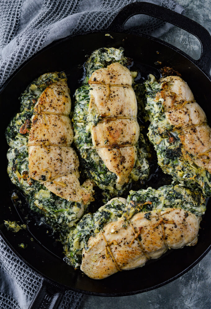 Four fully cooked spinach artichoke stuffed chicken sits in a black cast iron skillet. A gray textured napkin sits next to the pan.