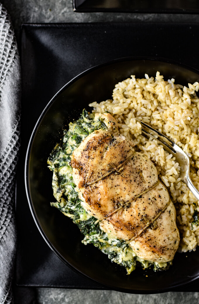 A close-up photo of a spinach artichoke stuffed chicken breast on a bed of rice. Three other stuffed chicken breasts on the top right side of the photo. All these are on black plates. A black bowl of rice is in the corner of the photo with a gray textured napkin beside them.