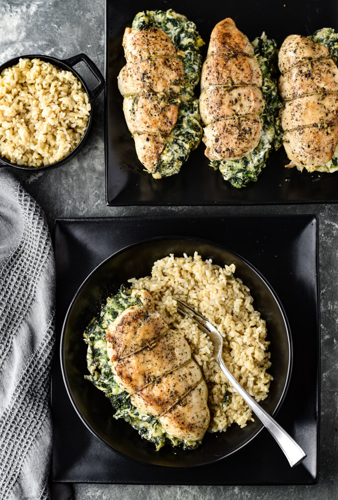 A spinach artichoke stuffed chicken breast rests on a bed of rice. Three more stuffed breasts sit in the top portion of the photo. All are sitting on black plates. A black bowl of rice is in the left hand corner and a gray napkin sits next to them all.