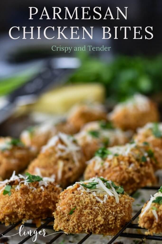 A white platter holds baked crispy chicken bites that have shredded parmesan and chopped parsley sprinkled on them. A bowl of Ranch dressing sits in the middle.