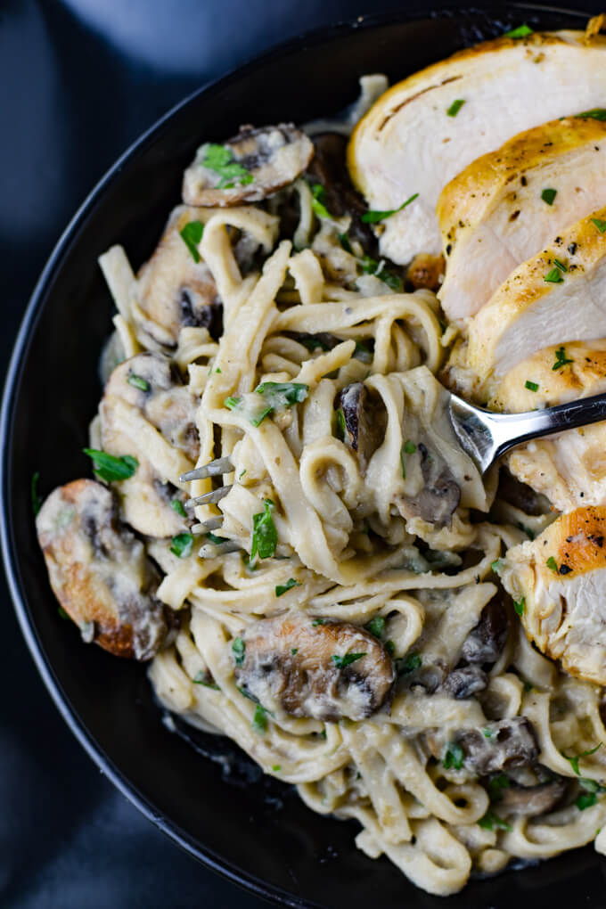 A black bowl of creamy cauliflower alfredo sauce with mushrooms and a sliced chicken breast.