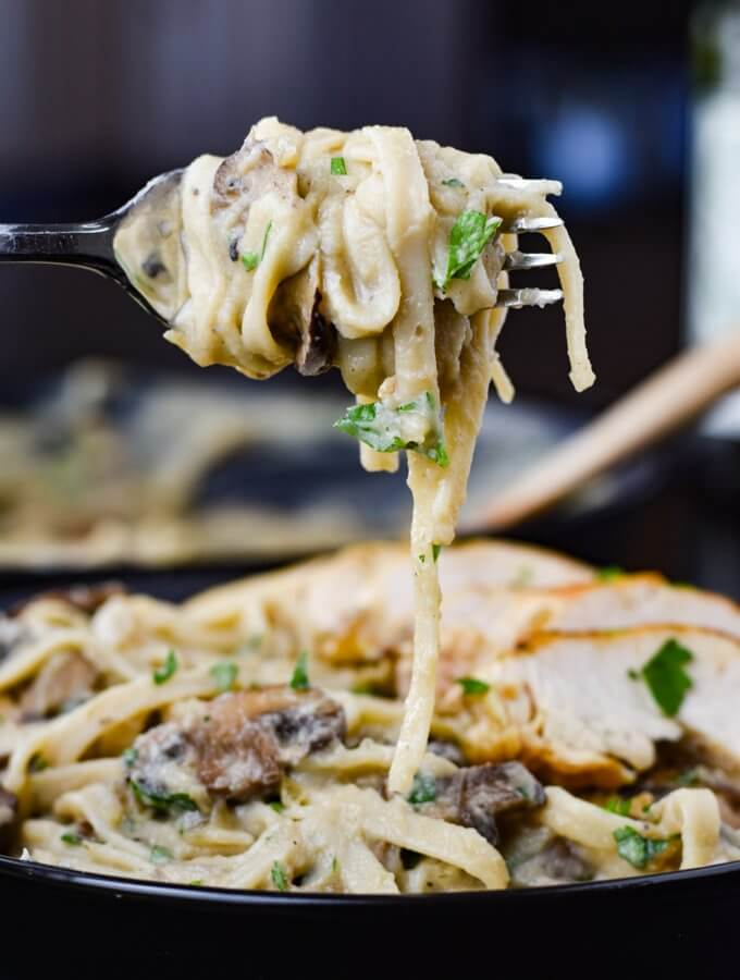 A fork full of creamy cauliflower alfredo with mushrooms hanging over a bowl of it. Sliced chicken breasts sits in the background.