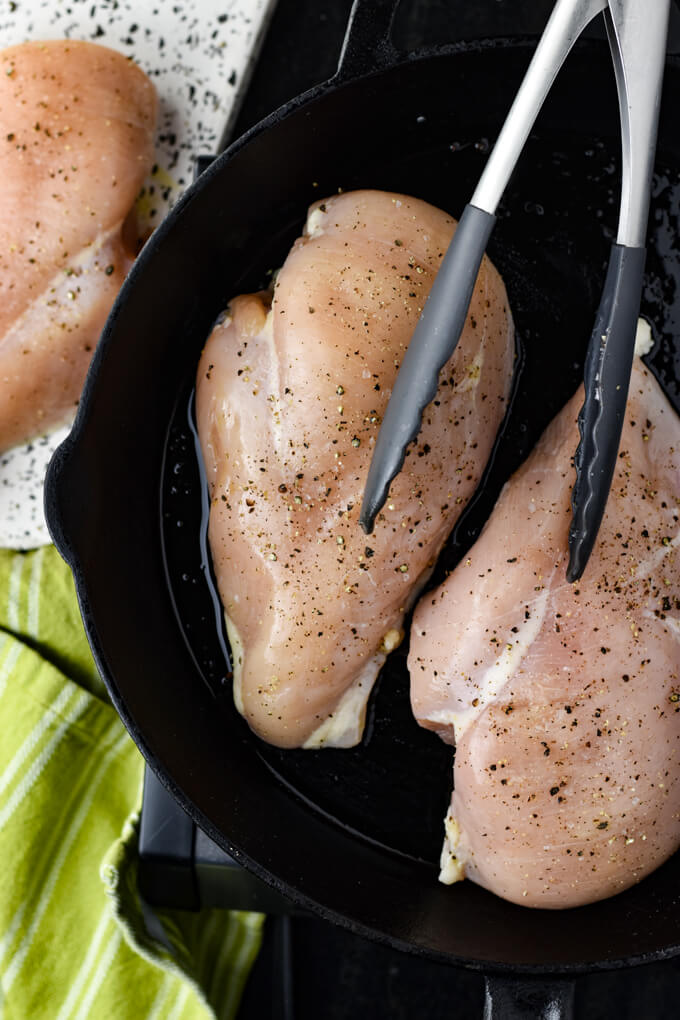 Two boneless skinless raw chicken breasts are in a black cast iron skillet with tongs sitting on them. Another chicken breasts sits on a white and black tray next to the skillet. A Green napkin is to the left.