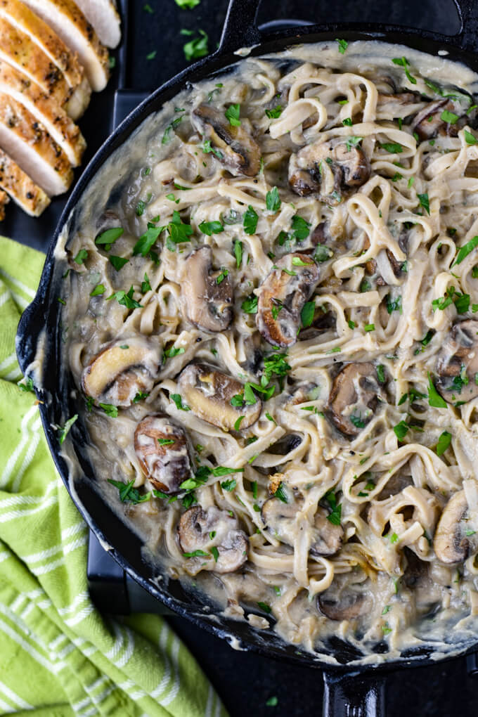 A black cast iron skillet with creamy cauliflower sauce, mushrooms and fettuccine noodles. A sliced chicken breast sits next to it.