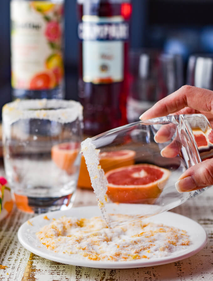 A glass is being rimmed with grapefruit zested sugar. Half grapefruits sit in the background.