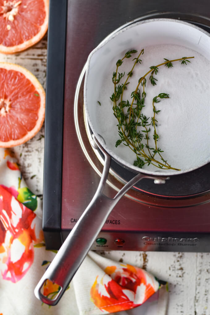 A pan of sugar and sprigs of thyme are ready to make simple syrup. Half a grapefruit and a colorful napkin sit next to the pan.