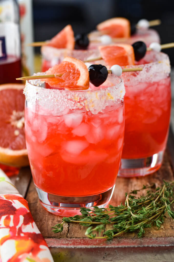 A front view of four glasses of fresh grapefruit cocktail. Fresh thyme sprigs sit next to one glass. There are garnishments of a cherry and slice of grapefruit sitting on the glass. A half grapefruit is in the background.