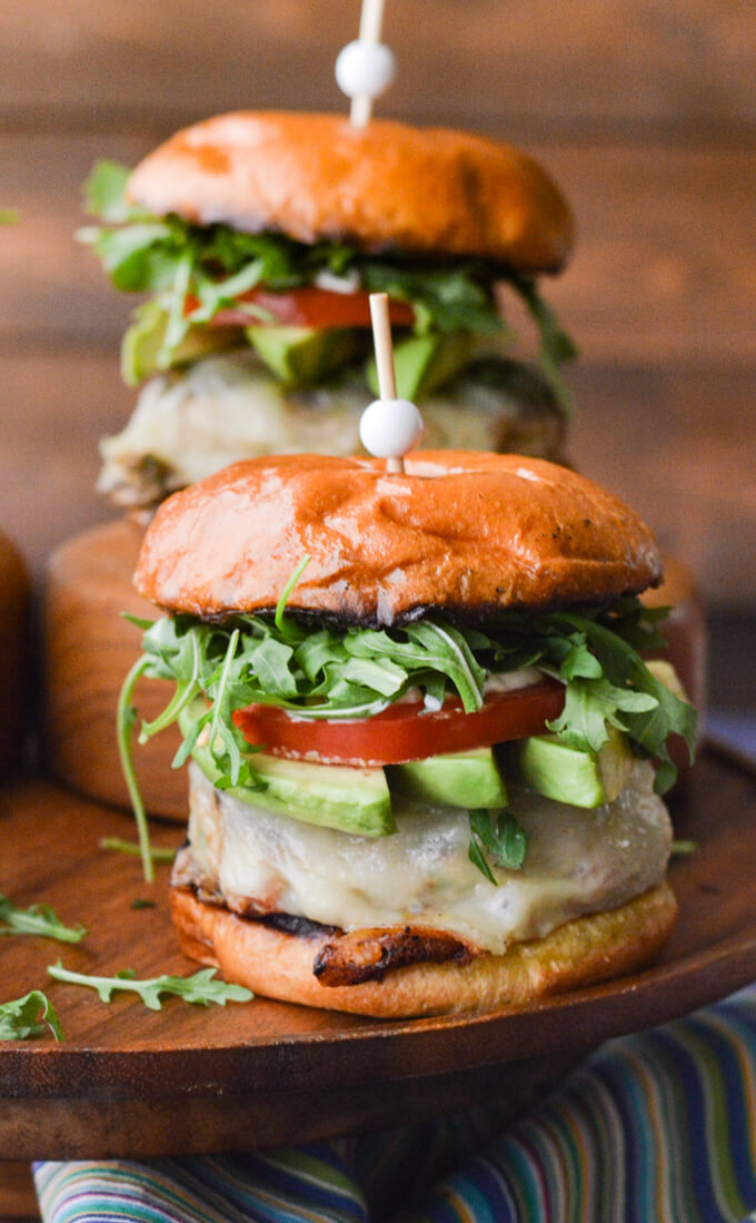 A front view of two turkey burgers with avocado slices, tomato and arugula sitting on a wooden tray with a blue striped napkin in front.