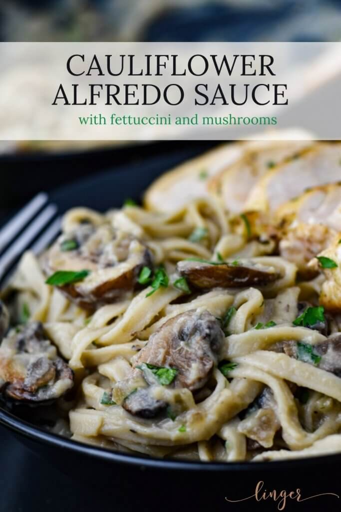Cauliflower Alfredo Sauce with Fettuccini and mushrooms in a bowl with sliced chicken breast next to it. A pan of the fettuccini is blurred in the background.