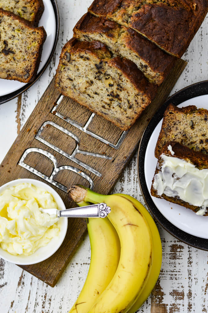 """Slices of banana bread sit on a """"bread"""" cutting board with a small bowl of butter. Three bananas and plates of banana slices sit next to the board. One slice is smeared with butter."""